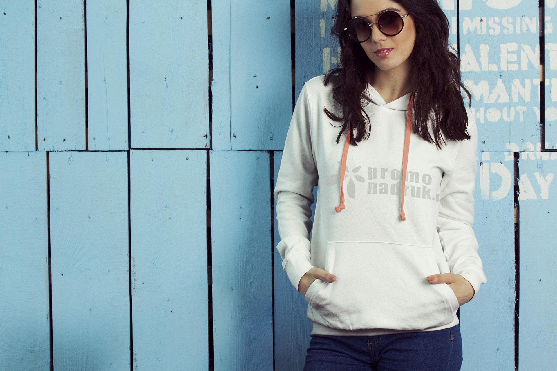 Modna młoda kobieta w białej bluzie z logo promonadruk.pl