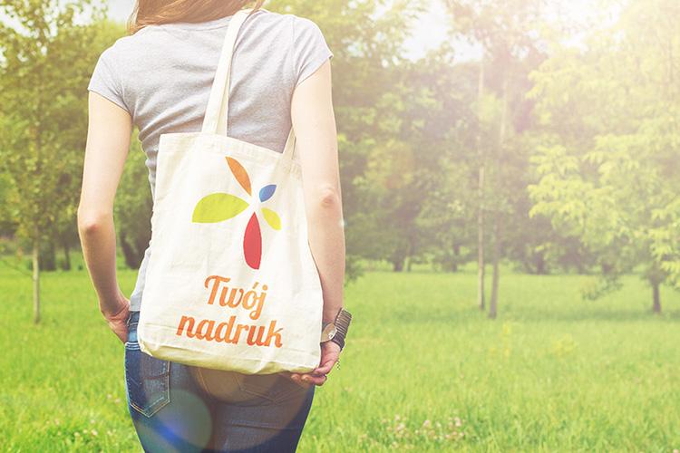 Młoda kobieta w parku, spaceruje z kremową torbą bawełnianą